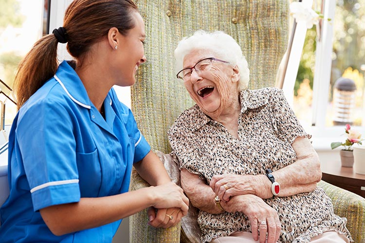 Image of a carer and an older person laughing