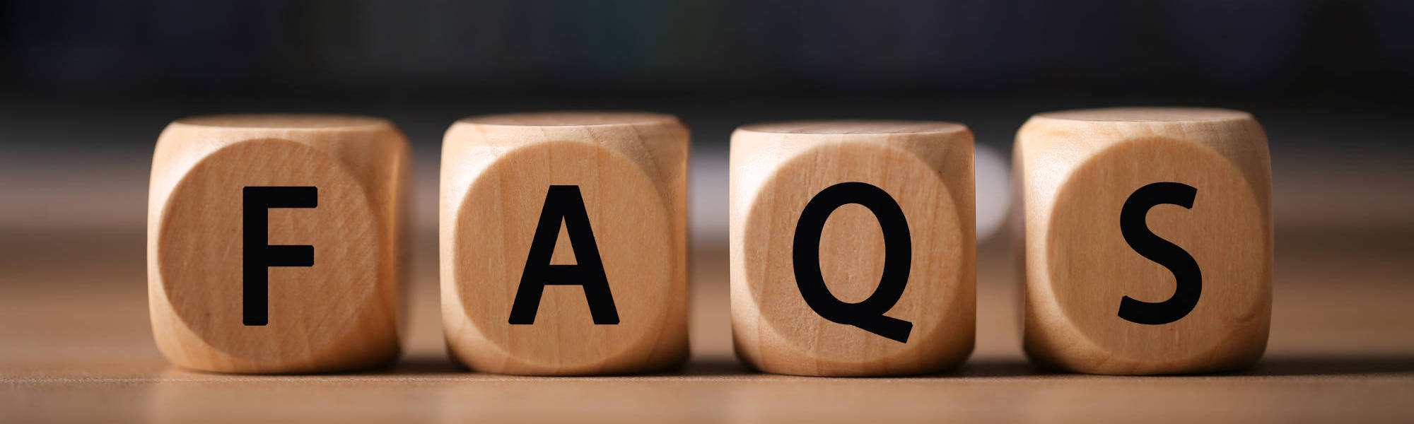 A photo of wooden blocks spelling out F-A-Q-S linking to the page section about frequently asked questions