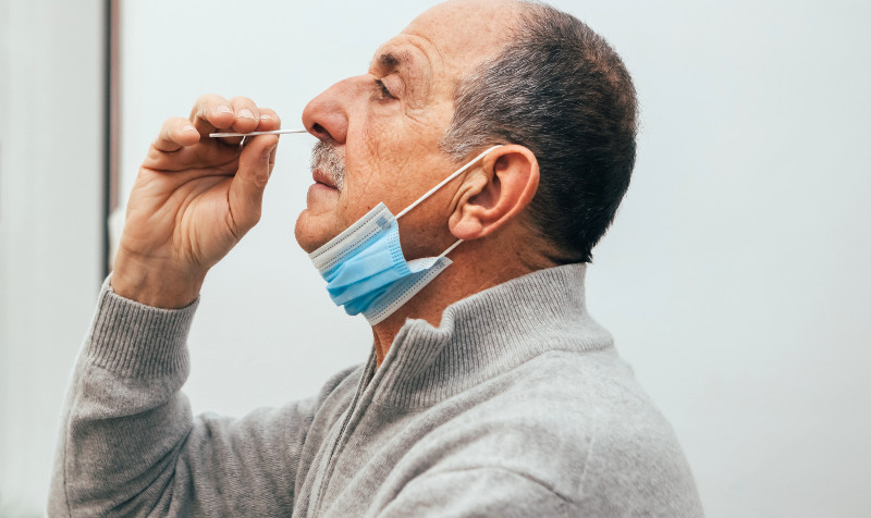 A photo of a man giving himself a nose swab for coronavirus linking to a page about community testing
