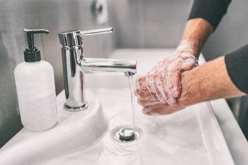A photo of a person washing their hands linking to the page section about staying safe from coronavirus