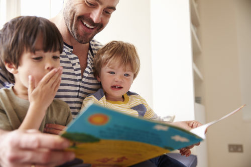 A photo of two young children being read a story linking to the page section about school