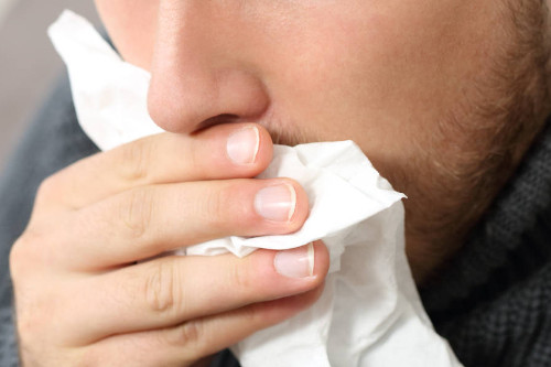 Photo of a man coughing into a tissue linking to the page section about coronavirus symptoms