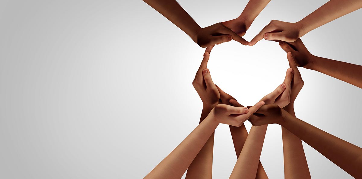 Image of the hands from many people forming the shape of a heart