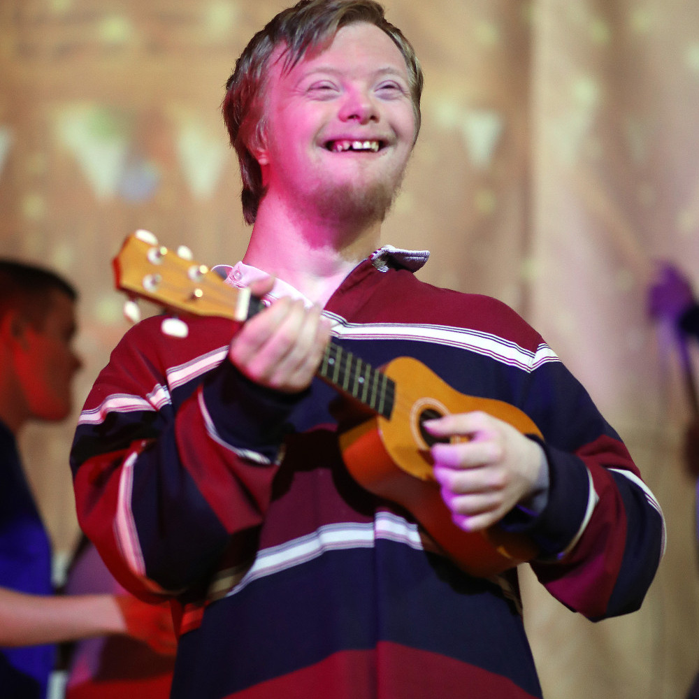 Image of a smiling person performing, which links to the Impact Drama Group page
