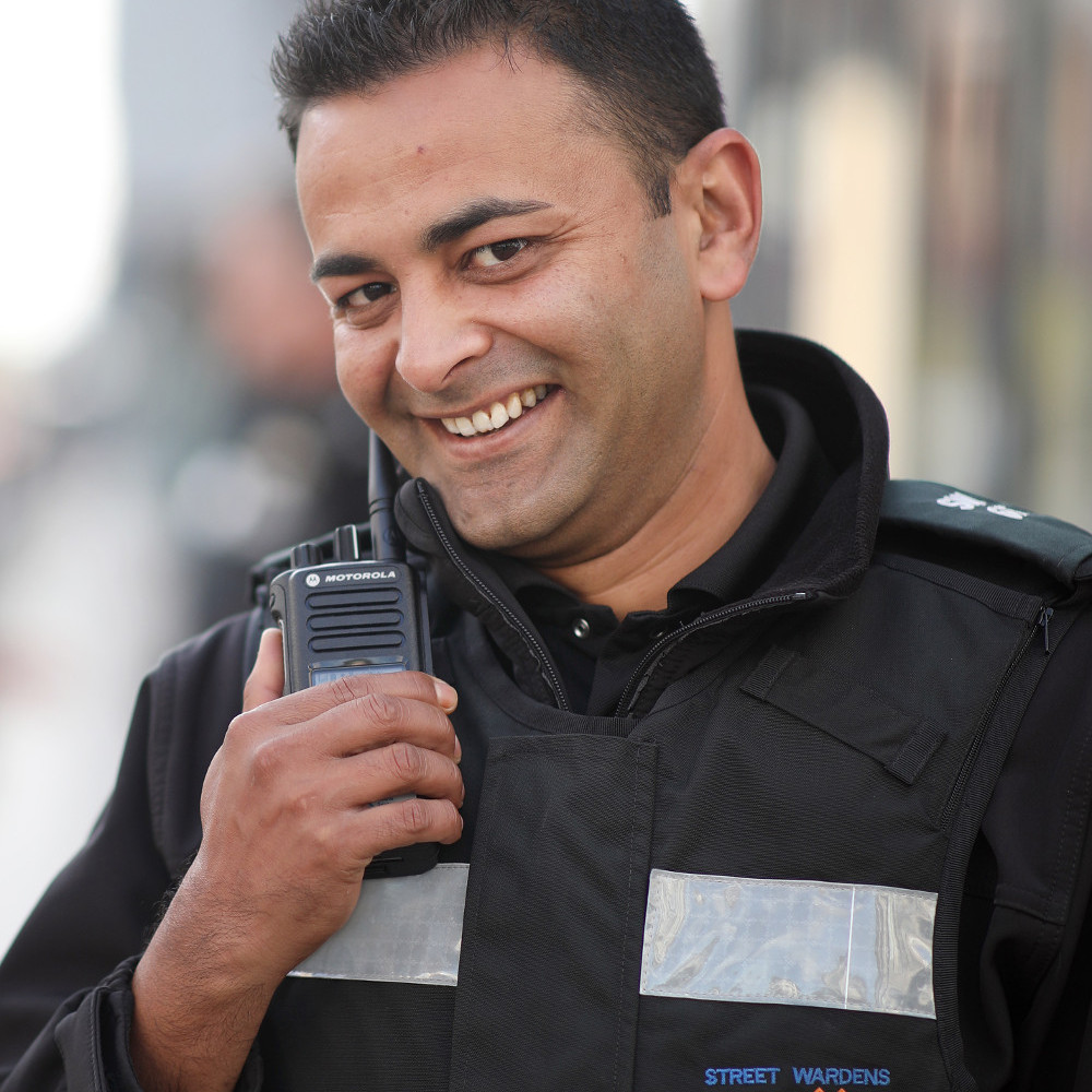 Image of a Street Warden using their radio, linking to the Street Wardens page