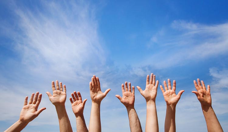 Image of hands raised against a blue sky