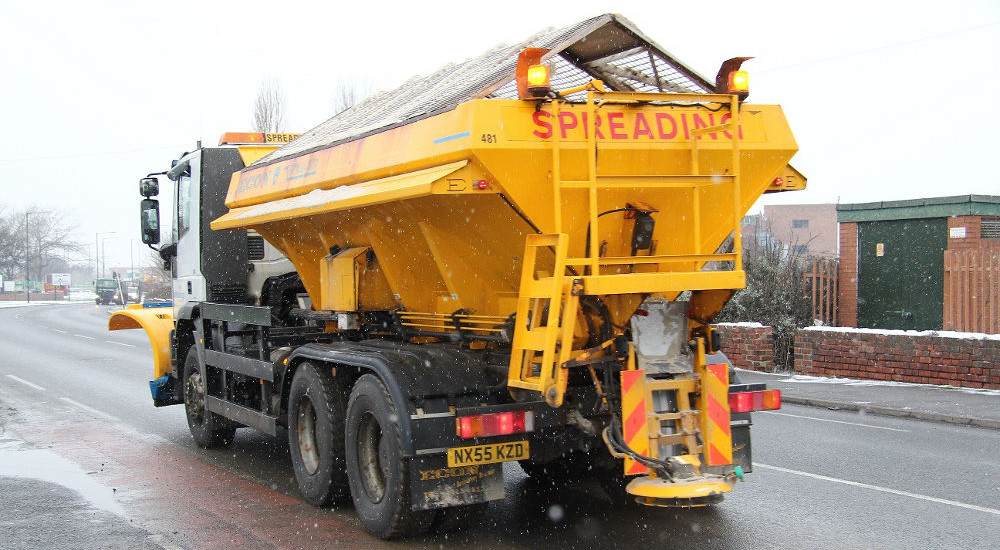 A photo of a gritter on the road in light snowfall linking to a page about gritting and winter weather