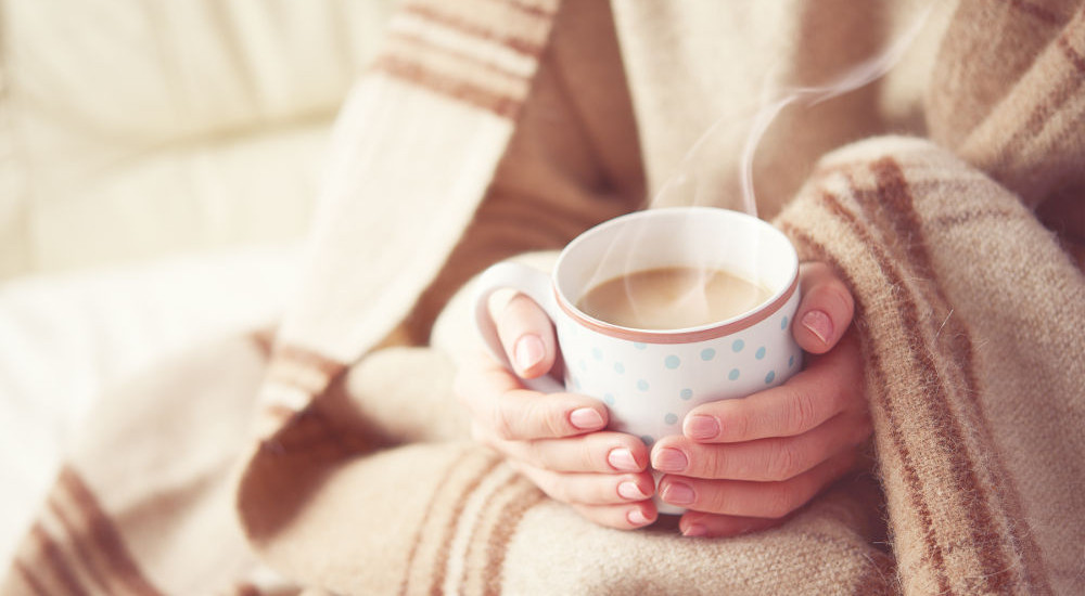 A photo of two hands under a blanket holding a hot drink linking to a page about health and wellbeing