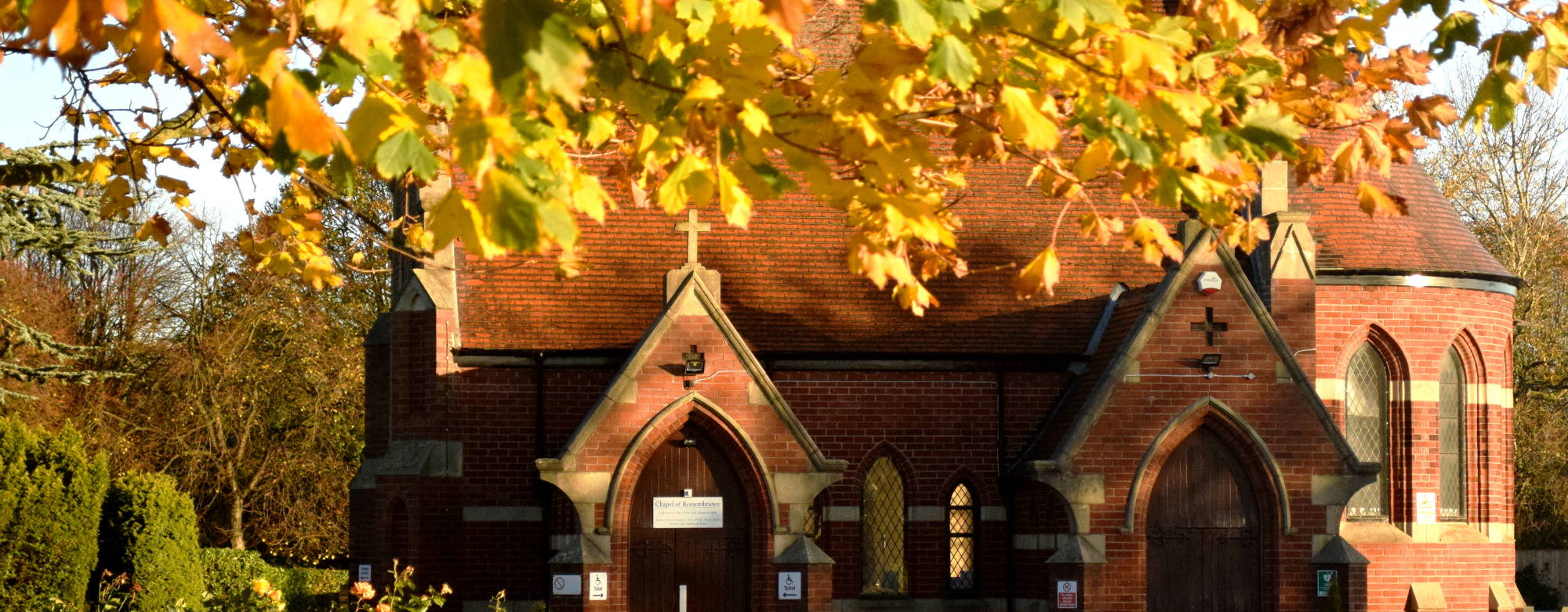 The Chapel of Remembrance at Teesside Crematorium in the sunlight and artistically framed by yellow autumn leaves