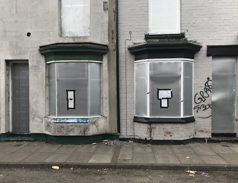 A photo of boarded up houses on Tennyson Street