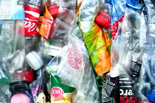 A photo of flattened plastic bottles ready to be recycled linking to a page about recycling plastic bottles